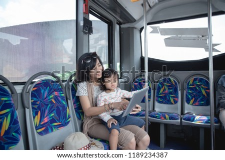 woman is holding her daughter in her lap and showing tablet to him while traveling with bus.