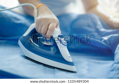 Woman is ironing blue clothes. #1105489304