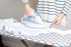 Woman is ironing clothes. The girl holds an iron on an ironing board with a ferry and irons things. Cleaning service of the apartment