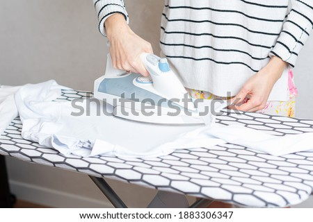 Woman is ironing clothes. The girl holds an iron on an ironing board with a ferry and irons things. Cleaning service of the apartment Photo stock ©
