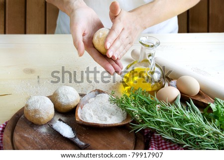 Woman is kneading dough balls for pizza or pastry, pasta preparation in the bakery . Ingredients for dough: Olive oil, salt and herbs with flour