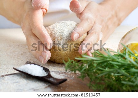 Woman is kneading fresh dough balls in the bakery. Ingredients for dough: salt, olive oil and fresh herbs