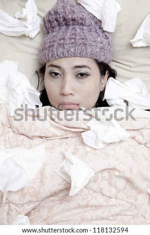 Woman is laying on her bed, wearing winter hat due to flu winter