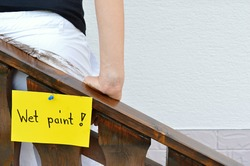 Woman is leaning at a wet painted handrail. With copy space on the right.