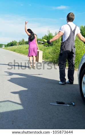 Woman is leaving mechanic alone near the broken car.