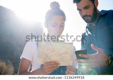 Woman is looking at a map and points as the man standing next to her holds a phone, they are both in the desert