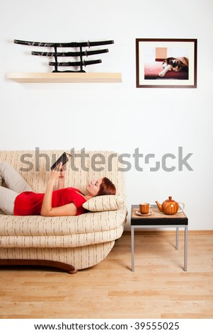 Woman is lying on a sofa at home and reading a book. Image on the wall was photographed by me.