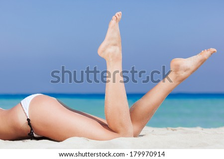 Woman is lying on the beach. Legs close-up