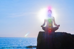 Woman is meditating with glowing seven chakras on stone at sunset. Silhouette of woman is practicing yoga at sunset on the beach. Kundalini meditation.