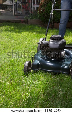 Woman is mowing her lawn with lawn mower in her back yard
