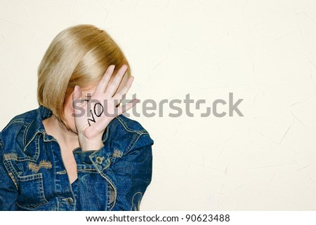"woman is on defensive inscription ""no"" on hand"