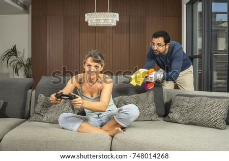 woman is playing video games while man is annoyed that he has to clean the house alone