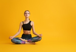 Woman is practicing yoga and meditation on color background.