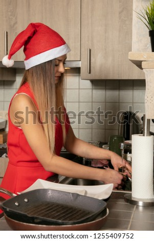woman is preparing for Christmas, she washes dirty dishes
