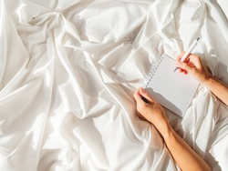 Woman is preparing to write or draw in diary. Top view on crumpled bed sheet and notepad with white paper pages. Practice of positive writing at morning after waking up. Flat lay with copy space.