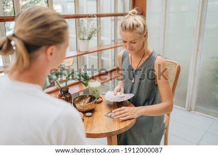 Woman is reading Tarot cards in cafe. Selective focus. Blurred foreground and background Photo stock ©