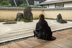 Woman is relaxing in a zen garden in Japan