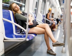 Woman is resting with phone in the train in the underground.
