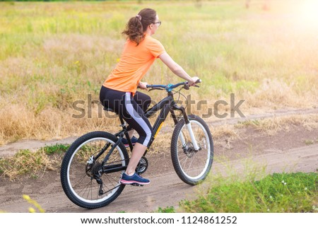 Woman is riding a bicycle, an active lifestyle. Active way of life, cycling. #1124861252