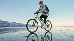 Woman is riding bicycle on the ice. Girl is dressed in a silvery down jacket, cycling backpack and helmet. Ice of the frozen Lake Baikal. Tires on bike are covered with spikes. Traveler is ride cycle.