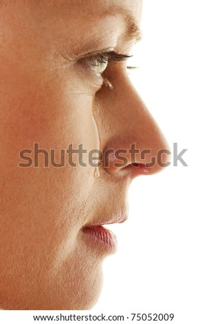 Woman is sad and cries. Teardrop on his cheek.