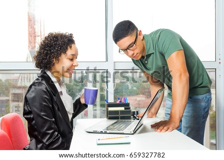 Woman is sitting and holding a mug. Young employee is standing and looks at laptop screen. #659327782