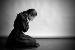 Woman is sitting in profile on an old cracky floor. She is sad and depressed, crying and covering her face with hands. Studio paper  background in behing her.