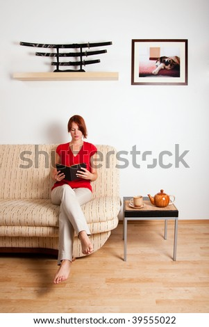 Woman is sitting on a sofa at home and reading a book. Image on the wall was photographed by me.