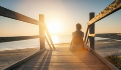 woman is sitting on a wooden path to the Baltic sea at sunset and relaxe the ocean view