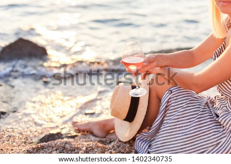 Woman is sitting on sea beach with wineglass of pink wine at sunset in summer vacation in resort. Tourist girl in striped dress with straw hat is enjoying life, relaxing, drinking, traveling. Stock photo ©