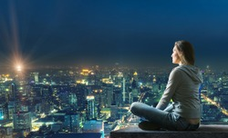 Woman is sitting over the city