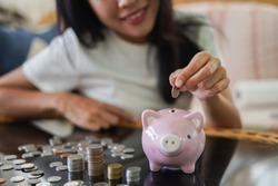 Woman is smiling and hand putting coin into piggy bank, Finance or Savings concept.
