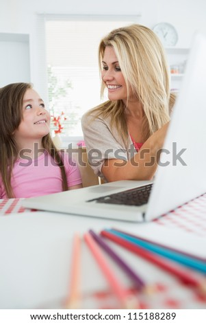 Woman is smiling at her daughter by the laptop in the kitchen