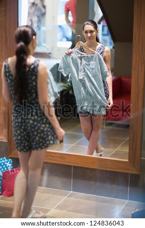 Woman is standing in front of the mirror with clothes in the changing room