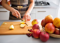 Woman is standing in her kitchen, preparing apples to use to make applesauce and other fruit preserves