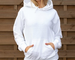 Woman is standing in white hoodie with hands in pockets in front of camera. She is posing for clothing mockup. On her hoodie is empty space for design or incription.  Sweatshirt hood template