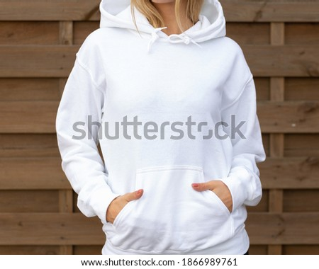 Woman is standing in white hoodie with hands in pockets in front of camera. She is posing for clothing mockup. On her hoodie is empty space for design or incription.  Sweatshirt hood template Foto stock ©