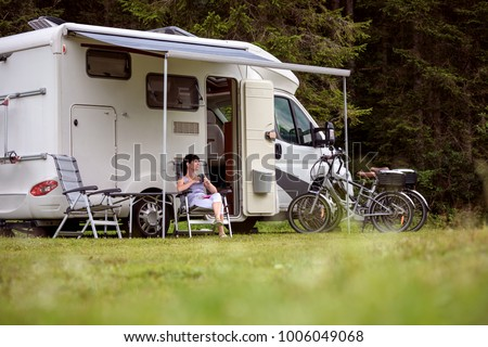 Woman is standing with a mug of coffee near the camper. Caravan car Vacation. Family vacation travel, holiday trip in motorhome RV #1006049068