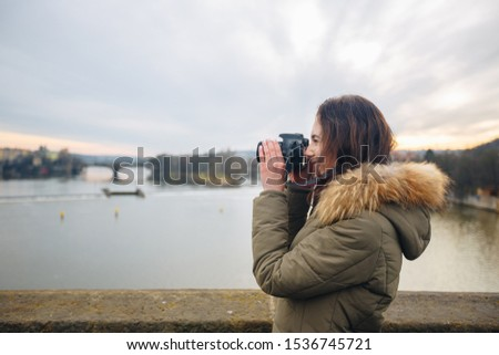 Woman is taking pictures on the Charles bridge in Prague. Young beautiful girl tourist stands on the Charles Bridge in Prague in the Czech Republic and takes photos of beautiful city views.