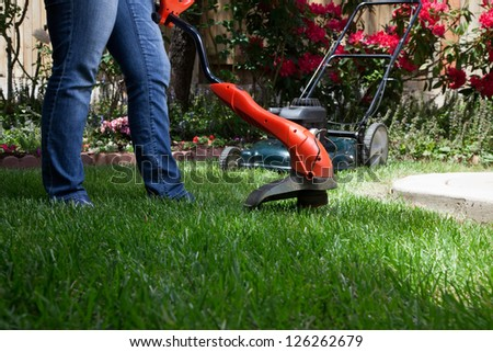 Woman is trimming her lawn with electric edge trimmer.