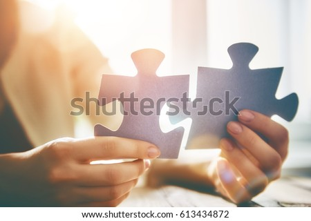 Woman is trying to connect couple puzzle piece. Symbol of association and connection. Concept of business strategy.