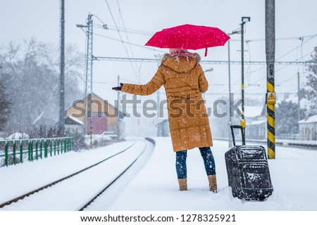Woman is waiting at the railroad station for a delayed train during snowstorm.