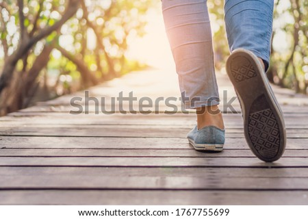 Woman is walking on small wood bridge to nature walk way with sunlight flare background.