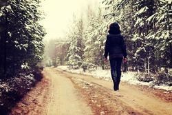 Woman is walking through forest in wintertime. Alone woman is going in cold day.