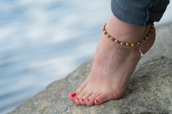 Woman is wearing handmade anklet, in a natural environment, in a bank of river.