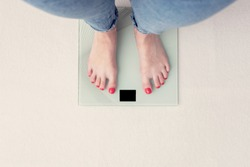 Woman is weighed on scales, female feet, top view, cropped image, toned