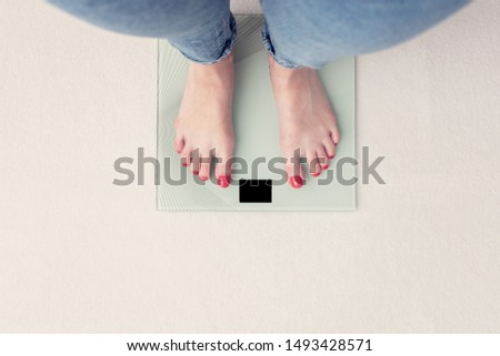 Woman is weighed on scales, female feet, top view, cropped image, toned Photo stock ©
