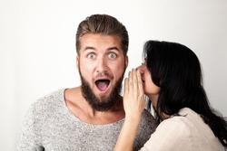 Woman is whispering a secret into her friends ear