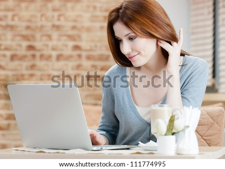 Woman is working on the laptop at the internet cafe