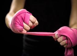 Woman is wrapping hands with pink purple boxing wraps. Isolated on black with red nails. Strong hand and fist, ready for fight and active exercise. Women self defense.